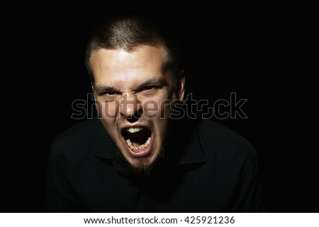 Angry man screaming. Terrible nasty man. A man in a black shirt. Male emotional portrait.