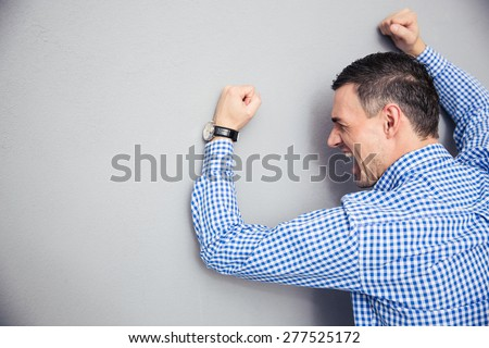 Angry man shouting and hitting gray wall - stock photo
