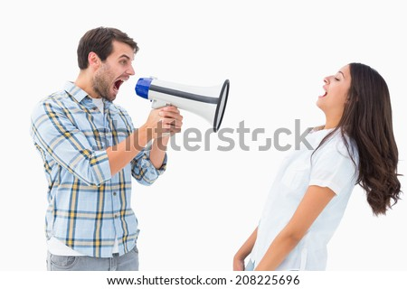Angry man shouting at girlfriend through megaphone on white background - stock photo