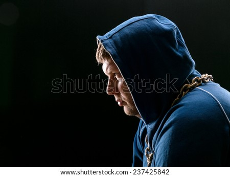 Angry man, sitting with hood on - stock photo