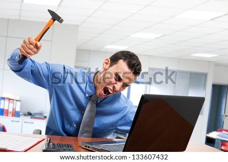 Angry man smashing his laptop - stock photo