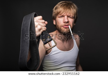 Angry man threatens with belt. Concept: Violence in the family. Studio portrait over black background  - stock photo