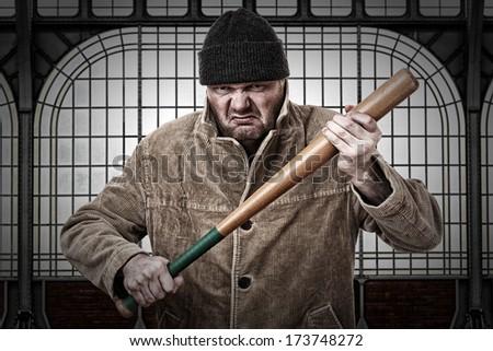 Angry man with baseball bat - stock photo