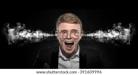 Angry man with smoke or fume coming out from his ears on dark background. - stock photo