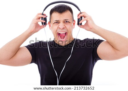 angry man yelling and shouting listening to loud music with headphones - stock photo