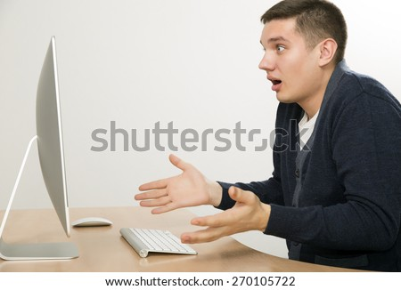 Angry man yelling on computer screen. Young man expresses anger fury sitting in front of large computer screen. Smart casual dress beige office desk, wireless keyboard and mouse, light grey background - stock photo