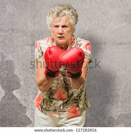 Angry Mature Woman Wearing Boxing Gloves, Indoors - stock photo