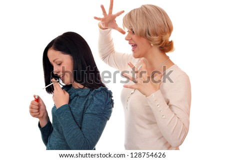angry mother finds out that her daughter smokes - stock photo