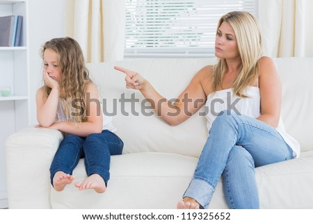 Angry mother scolding her daughter - stock photo