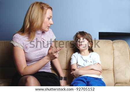Angry mother talks to her son, give him a warning - stock photo