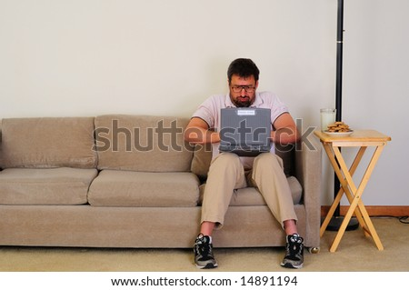 angry nerd types email in boring setting - stock photo