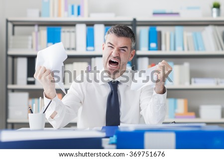 Angry nervous businessman working at office desk overloaded with paperwork, he is shouting at camera, overwork and stressful job concept - stock photo