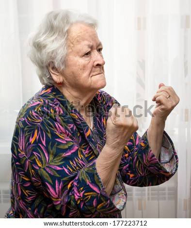 Angry old woman making fists