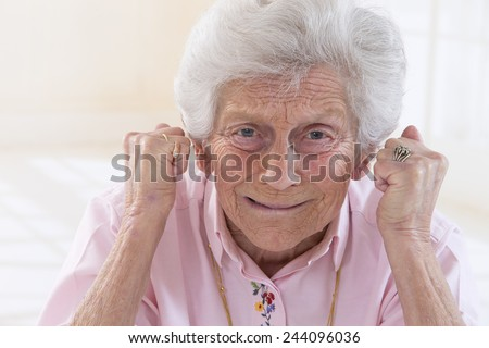 Angry old woman making fists - stock photo