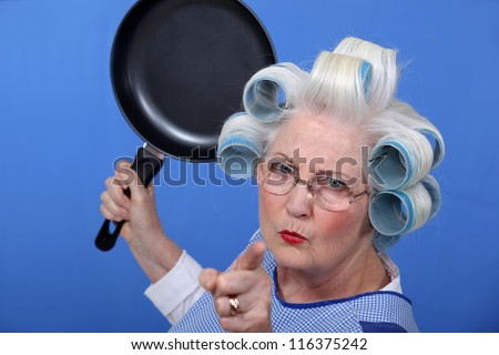 Angry old woman with a frying pan - stock photo