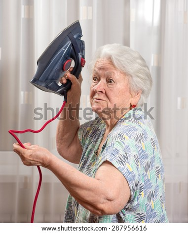 Angry old woman with an iron at home