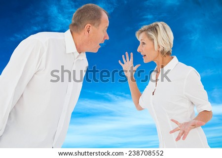Angry older couple arguing with each other against blue sky - stock photo