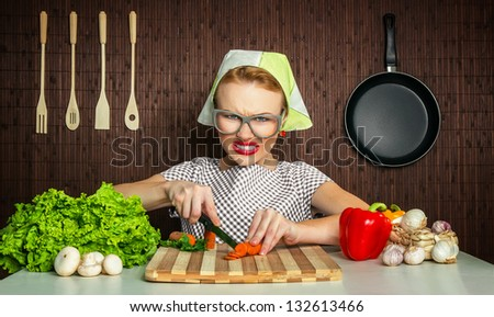 Angry or aggressive woman cook working in the kitchen cutting carrot - stock photo