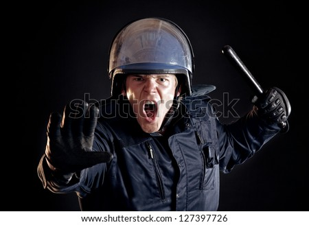 Angry police officer with nightstick telling the violent crowd to stop - stock photo