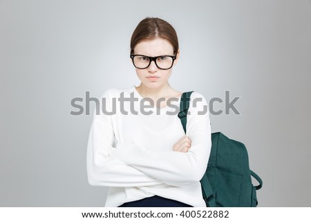 Angry pretty girl student in glasses with backpack standing with arms crossed - stock photo