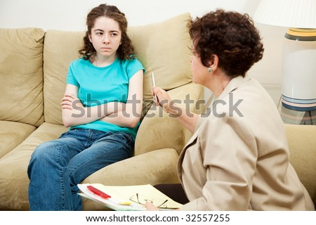 Angry, rebellious teen girl talking to a counselor. - stock photo