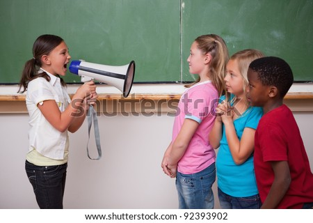 Angry schoolgirl screaming through a megaphone to her classmates in a classroom - stock photo