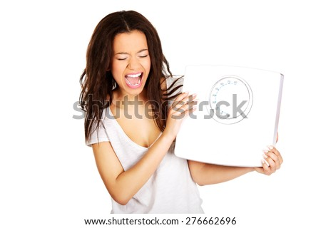 Angry screaming african woman holding a scale. - stock photo