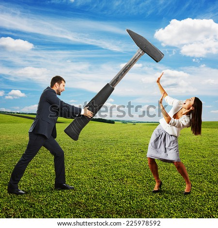 angry screaming man holding big hammer and hitting scared woman. photo at outdoor