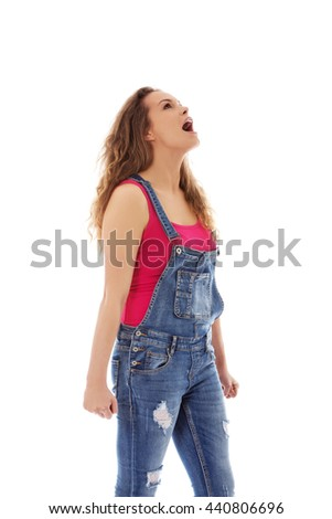 Angry screaming young woman with clenched fist - stock photo