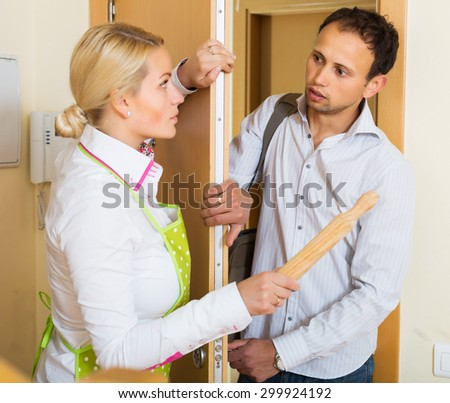 Angry serious girl threatens with rolling-pin for a frightened man - stock photo