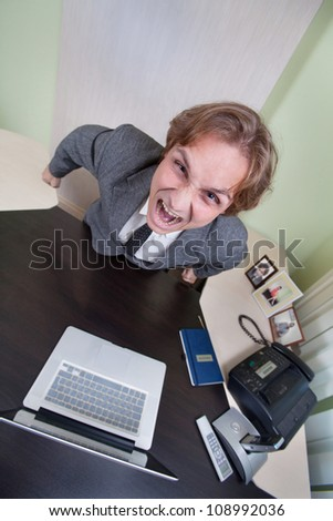Angry shouting businessman on the office background. - stock photo