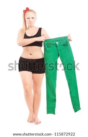 Angry 40 size girl holding 36 size trousers - stock photo