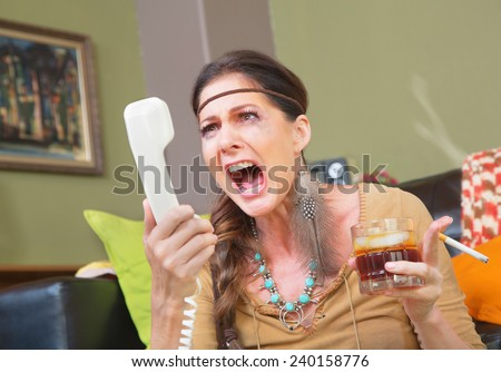Angry smoker with drink yelling into telephone - stock photo