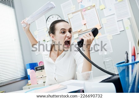 Angry stressed businesswoman on the phone screaming out loud. - stock photo