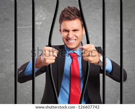 angry strong businessman bending the bars of his prison trying to get out