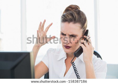 Angry stylish businesswoman on the phone in bright office - stock photo
