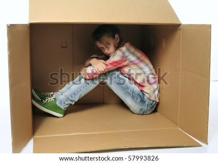 Angry teenage girl siting in box and irritating - bad mood, injury - stock photo