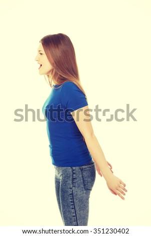 Angry teenage woman screaming loud. - stock photo