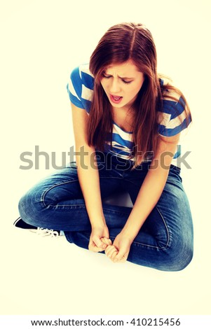 Angry teenage woman sitting on the floor and screaming  - stock photo