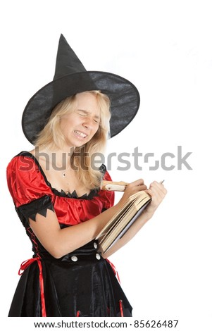 angry teenager girl in Halloween witch reads magic book - stock photo