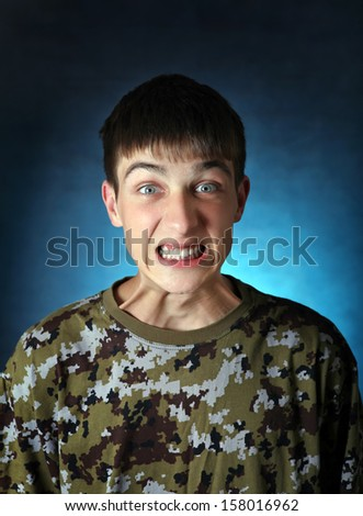 Angry Teenager in camouflage t-shirt on the Dark Background - stock photo