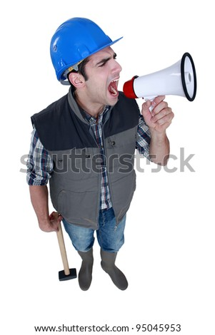 Angry tradesman yelling into a megaphone - stock photo