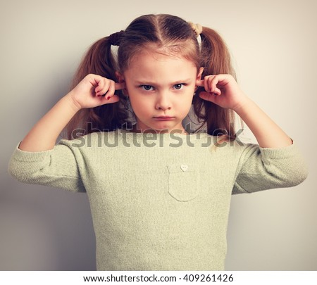 Angry unhappy kid girl covered ears the fingers and gesturing that not want to listen. Vintage toned portrait - stock photo