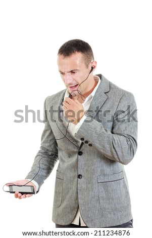 angry unhappy man in suit with headset and telephone - stock photo