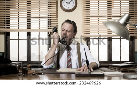 Angry vintage businessman shouting on the phone working at office desk. - stock photo