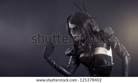 Angry witch with yellow eyes wearing black latex clothes - stock photo