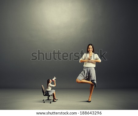 angry woman and calm woman over dark background - stock photo