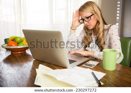 Angry woman doing her taxes at home - stock photo