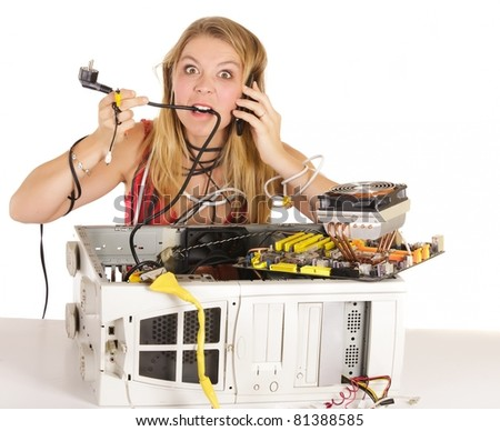 angry woman having problem with computer biting power cable and phoning support - stock photo