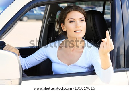 Angry woman in a car, boorishness on a road  - stock photo